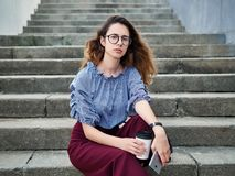 Young beautiful student girl in blue blouse and trendy glasses having fun with cup of coffee and smartphone posing on a stairs in. Young beautiful student lady stock photo