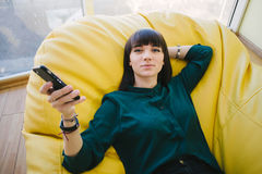 Young beautiful student resting in between training and holding a phone. Portrait in a room with an armchair bag. Young beautiful woman resting in between work Stock Image
