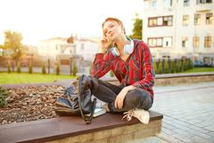 Young beautiful student wearing a checkered shirt headphones and a backpack resting on the street between classes. Beautiful redhead girl stock images