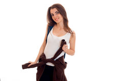 Young beautiful student woman in brown sports clothes and blue backpack on her shoulder smiling on camera isolated on Royalty Free Stock Photo