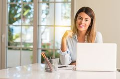 Young beautiful student woman with laptop at table, at home stock image