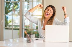 Young beautiful student woman with laptop at table, at home royalty free stock photos