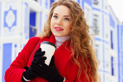 Young, beautiful and stylish blonde hair girl in red coat drinking coffee on the city street. Womens fashion. Royalty Free Stock Images