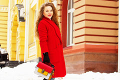 Young, beautiful and stylish blonde hair girl in red coat and with handbag walking through city streets. Womens fashion. Royalty Free Stock Photos