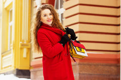 Young, beautiful and stylish blonde hair girl in red coat and with handbag walking through city streets. Womens fashion. Stock Photo