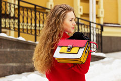 Young, beautiful and stylish blonde hair girl in red coat and keeping handbag on her back. Womens fashion. Stock Photography