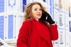 Young, beautiful and stylish blonde hair girl in red coat talking on her phone. Womens fashion. Stock Images
