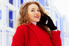 Young, beautiful and stylish blonde hair girl in red coat talking on her phone. Womens fashion. Royalty Free Stock Photos