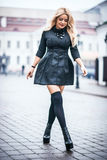 Young beautiful stylish classy girl wearing black dress. Standing and posing in the city Royalty Free Stock Image