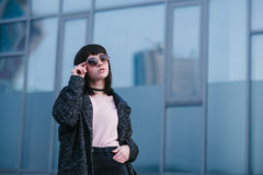 Young, beautiful and stylish dressed girl in the spring which adjusts his glasses and posing on urban background. Portrait and stylish dressed girl in the spring Stock Photography
