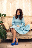 Young beautiful stylish girl in a blue dress sitting on a sofa Royalty Free Stock Image