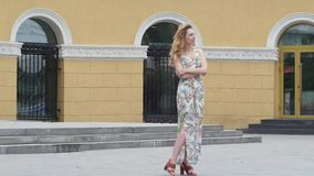 Young beautiful stylish girl posing at the summer city streets on a sunny day. stock video footage