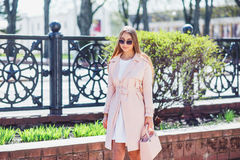 Young beautiful stylish girl walking and posing in white dress and pink coat in city . Outdoor summer portrait of young classy wom Royalty Free Stock Photo