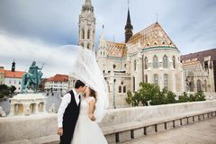 Young beautiful stylish pair of newlyweds kissing by the Fisherman`s Bastion in Budapest, Hungary royalty free stock images
