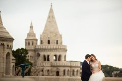 Young beautiful stylish pair of newlyweds sitting by the Fisherman`s Bastion in Budapest, Hungary stock image