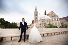 Young beautiful stylish pair of newlyweds walking by the Fisherman`s Bastion in Budapest, Hungary royalty free stock image
