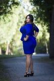 Young beautiful stylish plus size fashion model in blue dress outdoors, xxl woman on nature Stock Image