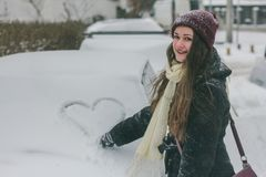 A young beautiful stylish woman paints a heart on a snow-covered car glass. royalty free stock photo