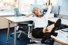 Young beautiful successful businesswoman resting, relaxing at workplace, over office background. Royalty Free Stock Photography