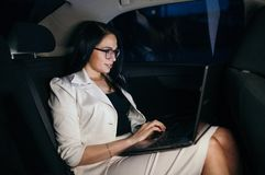 Young beautiful successful businesswoman sitting in the luxurious car and using laptop. Good Royalty Free Stock Photography