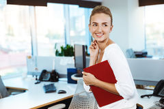 Young beautiful successful businesswoman smiling, posing, holding folder, over office background. Royalty Free Stock Photos