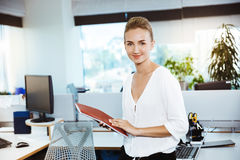 Young beautiful successful businesswoman smiling, posing, holding folder, over office background. Stock Photography