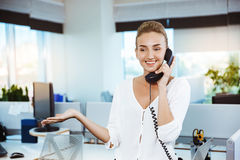 Young beautiful successful businesswoman smiling, speaking on phone, over office background. Stock Images