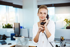 Young beautiful successful businesswoman smiling, speaking on phone, over office background. Stock Image
