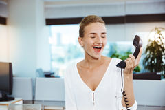 Young beautiful successful businesswoman smiling, speaking on phone, over office background. Royalty Free Stock Image