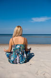 Young beautiful summer woman meditating on the sea Royalty Free Stock Images