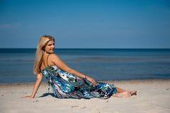 Young beautiful summer woman meditating on the sea Stock Photos