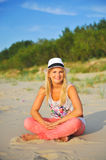 Young beautiful summer woman sitting on the beach Royalty Free Stock Image