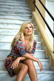 Young beautiful summer woman sitting on stairs Royalty Free Stock Image