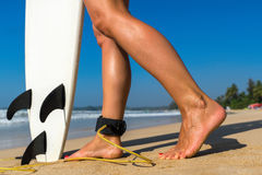 Young beautiful surfer girl on beach with surf board at day brea Royalty Free Stock Photography