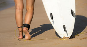 Young beautiful surfer girl on beach with surf board at day brea Royalty Free Stock Photos