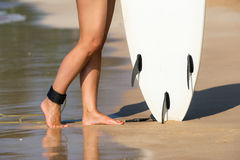 Young beautiful surfer girl on beach with surf board at day brea Stock Images