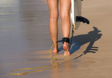 Young beautiful surfer girl on beach with surf board at day brea Stock Image