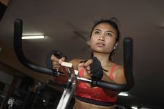 Young beautiful and sweaty Asian active woman training hard cycling and riding on static bike workout at gym. In sport fitness body care and healthy lifestyle Royalty Free Stock Images