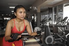 Young beautiful and sweaty Asian active woman training hard cycling and riding on static bike workout at gym Royalty Free Stock Photos