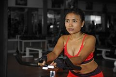 Young beautiful and sweaty Asian active woman training hard cycling and riding on static bike workout at gym Royalty Free Stock Photography