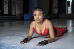 Young beautiful sweaty Asian woman in sport clothes stretching on gym dojo floor smiling posing corporate Stock Photos