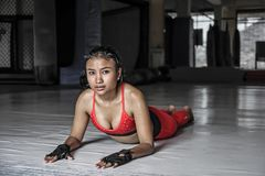 Young beautiful sweaty Asian woman in sport clothes stretching on gymm dojo floor smiling posing corporate Royalty Free Stock Image