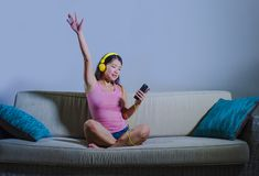 Young beautiful and sweet Asian Korean woman listening to music relaxed and happy sitting at home sofa couch holding mobile phone royalty free stock images