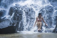 Young beautiful and sweet Asian woman in bikini getting body wet under stream of natural amazing waterfall sitting on rock feeling Stock Photo
