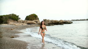 Young beautiful tanned woman with long hair in bikini walking on sandy beach at sunset. Young beautiful tanned woman with long hair in bikini walking on the stock video footage