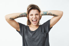 Young beautiful tattooed girl closing ears with hands shouting looking at camera over white background. Stock Images