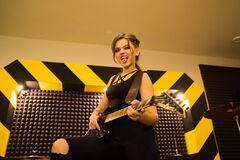 Young beautiful tattooed girl with a guitar, rock singer recording the sound in professional studio on the striped wall