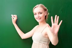 Young beautiful teacher shows five points Royalty Free Stock Photos