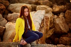 Young beautiful teen girl sitting on a stone by the sea royalty free stock photo