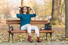 Young beautiful teenage girl sitting on the park bench and holding her hair Stock Photos